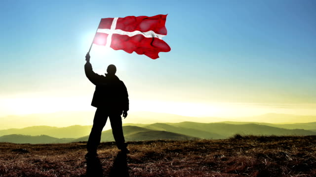 Successful silhouette man winner waving Denmark flag on top of the mountain peak, 4k cinemagraph video