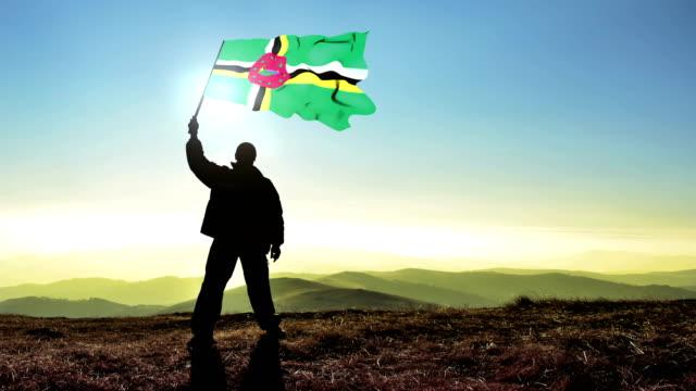 Successful silhouette man winner waving Dominican flag on top of the mountain peak. Cinemagraph LOOP background