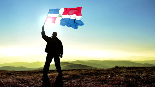 Successful silhouette man winner waving Dominican Republic flag on top of the mountain peak. Cinemagraph LOOP background
