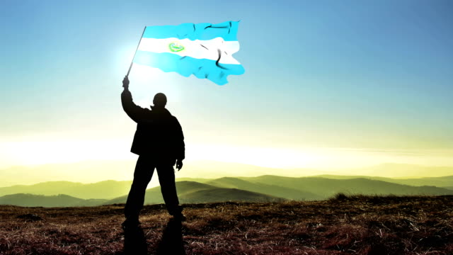 Successful silhouette man winner waving El Salvadorian flag on top of the mountain peak. Cinemagraph LOOP background