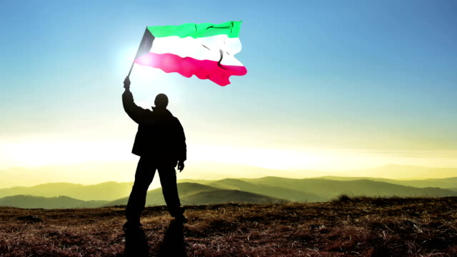 Successful silhouette man winner waving Kuwait flag on top of the mountain peak, 4k cinemagraph video