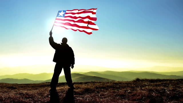 successful silhouette man winner waving liberia flag on top of the mountain peak, cinemagraph loop background - liberia video stock e b–roll