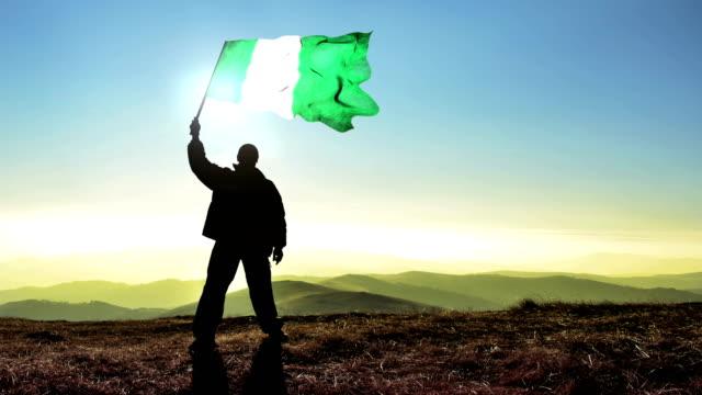 Successful silhouette man winner waving Nigeria flag on top of the mountain peak, Cinemagraph LOOP background video