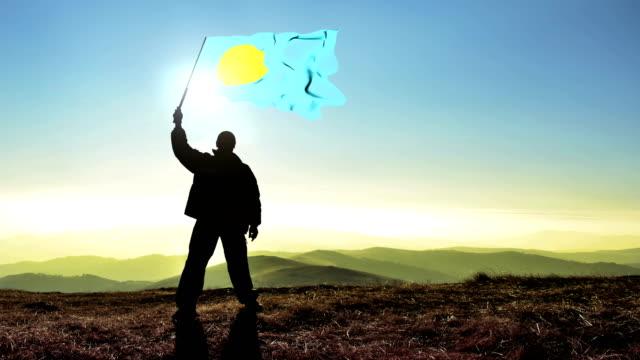vídeos y material grabado en eventos de stock de ganador de hombre exitoso silueta palau bandera sobre la cima de la montaña, fondo cinemagraph lazo - palaos
