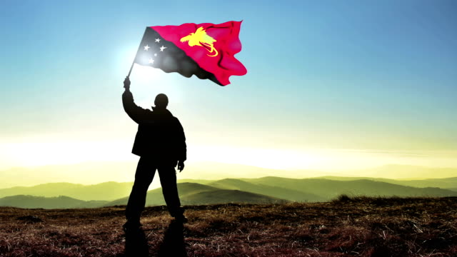 Successful silhouette man winner waving Papua New Guinea flag on top of the mountain peak, Cinemagraph LOOP background video