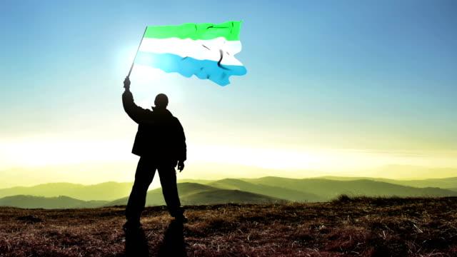 successful silhouette man winner waving sierra leone flag on top of the mountain peak, cinemagraph loop background - sierra leone video stock e b–roll