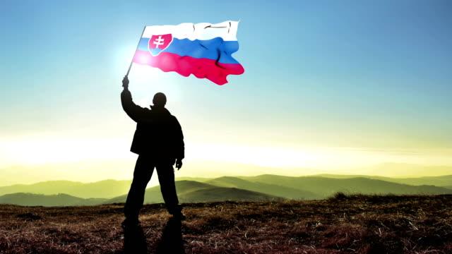 Successful silhouette man winner waving Slovak Republic flag on top of the mountain peak, Cinemagraph LOOP background