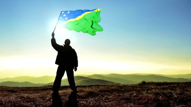 Successful silhouette man winner waving Solomon Islands flag on top of the mountain peak, Cinemagraph LOOP background