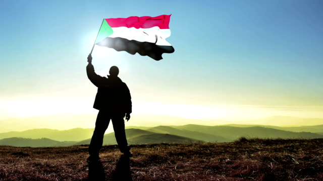 Successful silhouette man winner waving Sudan flag on top of the mountain peak, Cinemagraph LOOP background