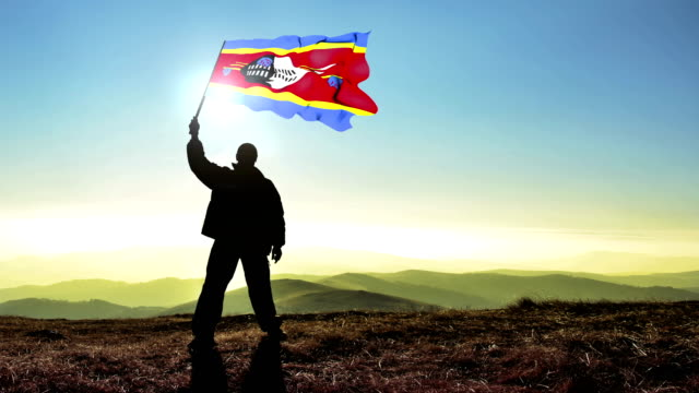 Successful silhouette man winner waving Swaziland flag on top of the mountain peak, Cinemagraph LOOP background video