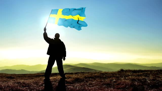 Successful silhouette man winner waving Sweden flag on top of the mountain peak, Cinemagraph LOOP background