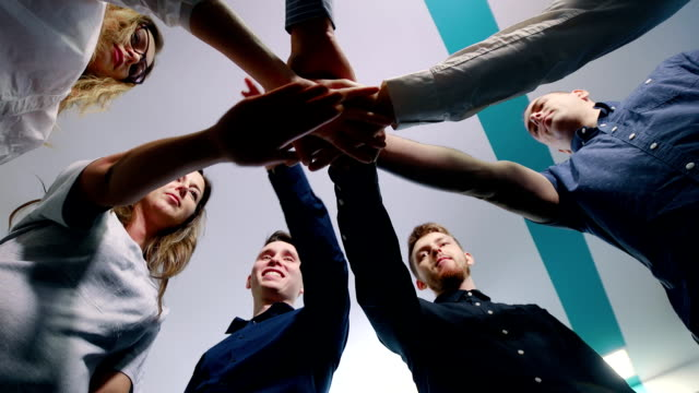 Successful team in office: many hands holding together standing in circle. Team building concept. Successful team in office: many hands holding together standing in circle. Team building concept obedience stock videos & royalty-free footage