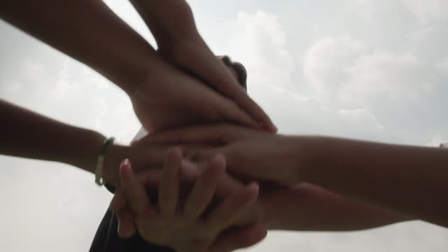 successful team: many hands holding together on sky background in slow motion - mano donna dita unite video stock e b–roll