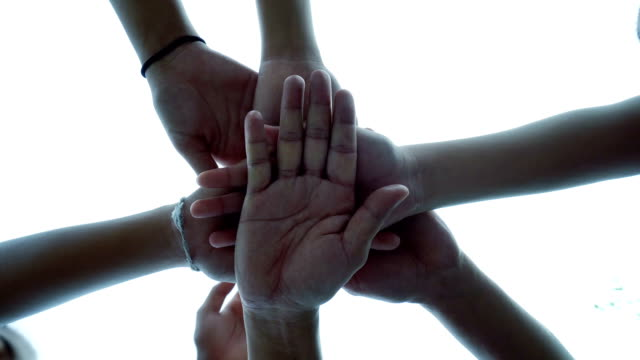 successful team: many hands holding together on sky background - mano donna dita unite video stock e b–roll