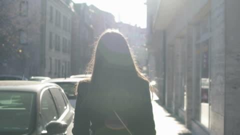 vidéos et rushes de femme réussie marchant lentement dans la rue, faisceaux de soleil lumineux l'éclairant - marcher