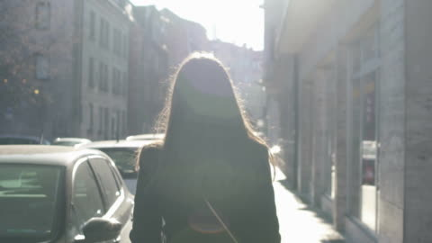 vídeos de stock e filmes b-roll de successful woman slowly walking down street, bright sun beams illuminating her - andar