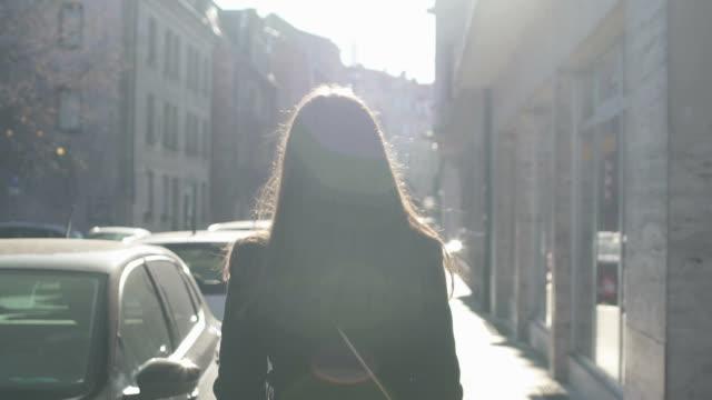 donna di successo che cammina lentamente per strada, raggi di sole luminoso che la illuminano - andare giù video stock e b–roll