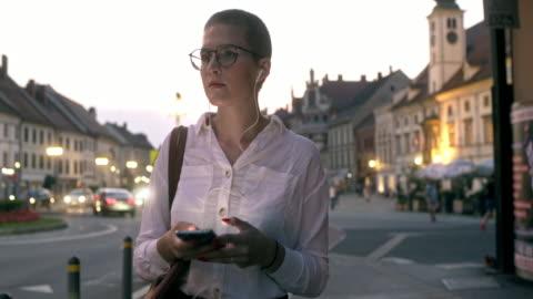 vídeos y material grabado en eventos de stock de ms mujer exitosa usando un teléfono inteligente mientras camina en la ciudad - toma mediana