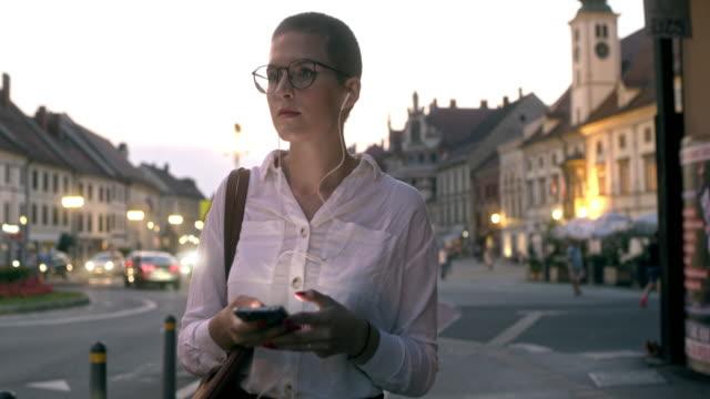 stockvideo's en b-roll-footage met ms succesvolle vrouw met behulp van een slimme telefoon tijdens het wandelen in de stad - medium filmcompositietype