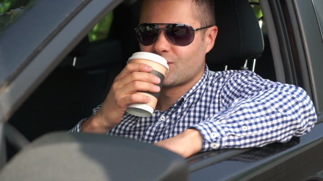 A successful young handsome man drinks coffee in a car video