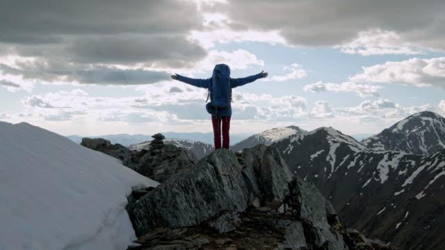 마운틴 피크에 성공적인 젊은 여성 배낭 오픈 암 - mountain top 스톡 비디오 및 b-롤 화면