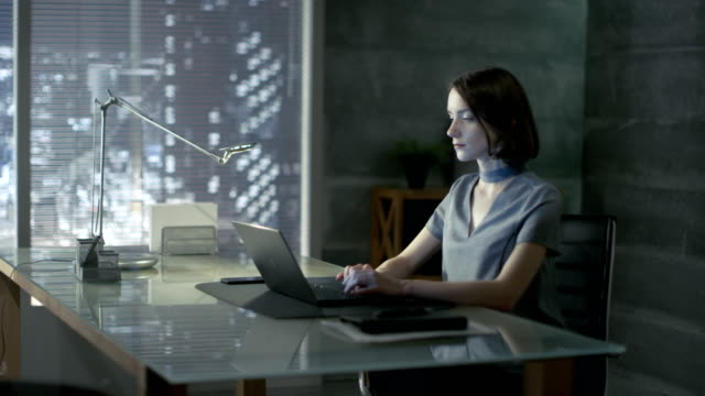 Successful Young Woman Sits in a Private Office At Her Desk and Works on a Laptop. Her Office is Done in Minimalist Style, is quite Dark and Has Window with Big City View. video