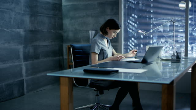 Successful Young Woman Sits in a Private Office At Her Desk and Works on a Laptop, Signs Important Documents. Her Office is Done in Minimalist Style, is quite Dark and Has Window with Big City View. video