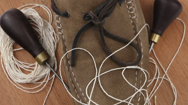 Suede shoes, awl and thread, shoe repair