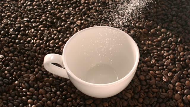 Zucker und Instant-Kaffee strömen in eine weiße Tasse in Zeitlupe gemischt – Video