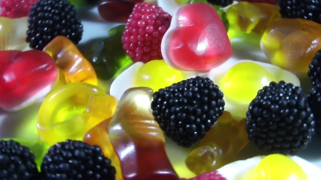 sugar color chewy gelatin candy rotating on table - sostanza gelatinosa video stock e b–roll