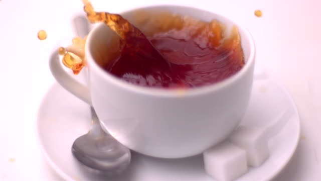 Sugar cube falling into tea and splashing video