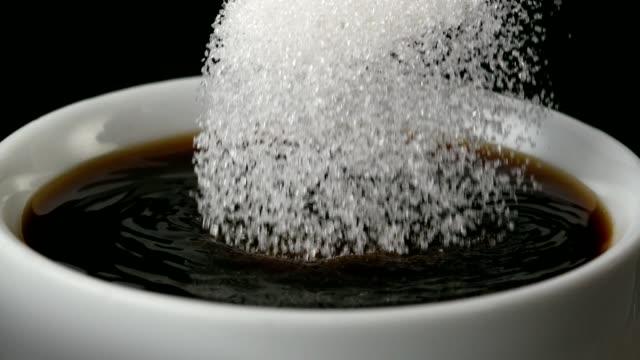 zucker gießen in schwarzen kaffee - close up - zucker stock-videos und b-roll-filmmaterial