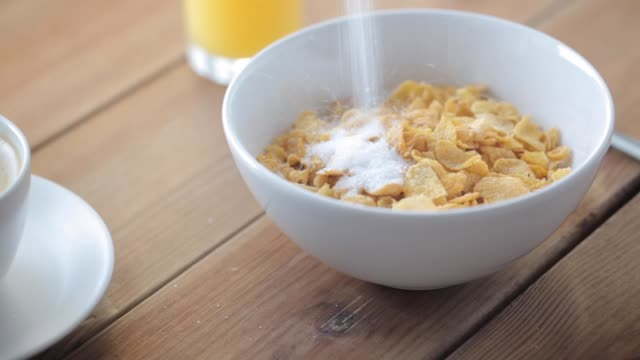 sugar pouring to corn flakes on wooden table - dolci video stock e b–roll