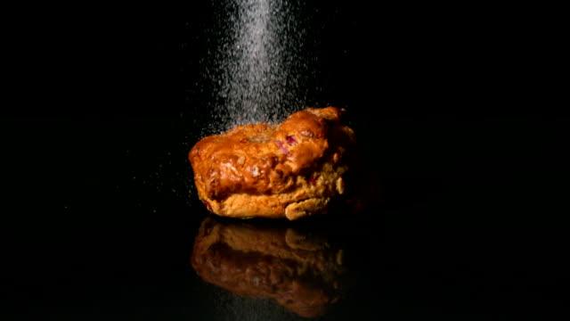 posypać cukrem na scone na czarnym tle - scone filmów i materiałów b-roll