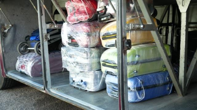 suitcases in luggage compartment of bus - rozładowywać filmów i materiałów b-roll
