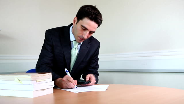 Suited male lawyer signing contracts video