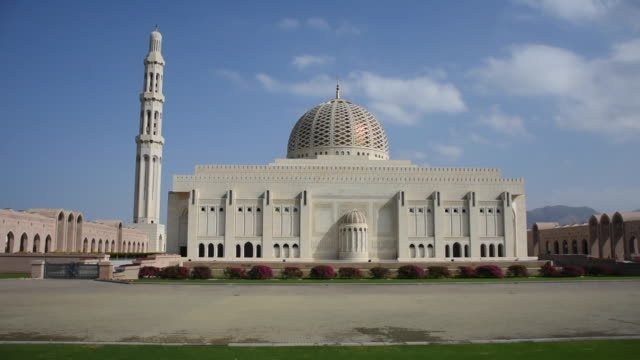 sultan qaboos grand mosque, muscat, oman during the afternoon in the blue sky and clouds and mountains in view - oman video stock e b–roll