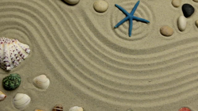 Summer background - shells, stars and stones on zigzag sand. Crane shot.
