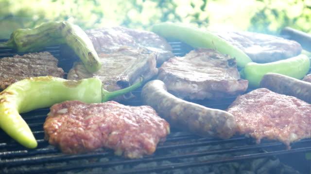 summer bbq grill t-bone steak and burgers - abbrustolito video stock e b–roll