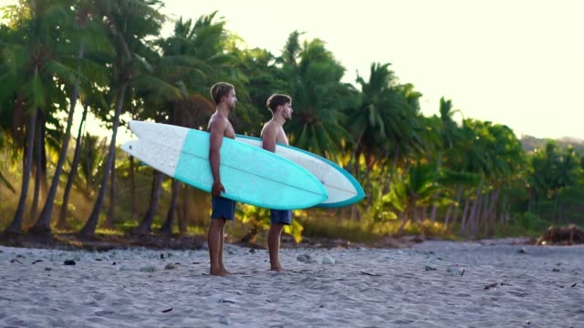 Summer beach lifestyle, young man going surfing. beautiful golden sunrise light. Slow motion