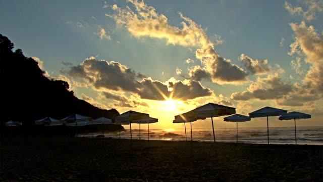 Summer Beach with umbrellas at Sunset near the sea coast. video