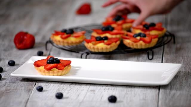 krem ve taze çilek ile yaz berry tartlets. parti için sağlıklı yaz pasta tatlı. - muhallebi stok videoları ve detay görüntü çekimi