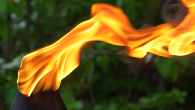 close up, dof: summer breeze blows the flame burning on the torch sideways. - simbolo concettuale video stock e b–roll