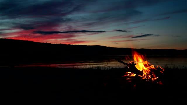 estate camino e il lago al tramonto - falò spiaggia video stock e b–roll