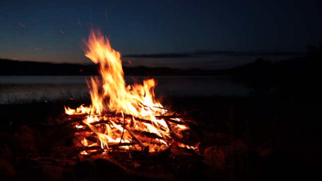 yaz kamp ateşi ve göl günbatımı - şömine odunu stok videoları ve detay görüntü çekimi