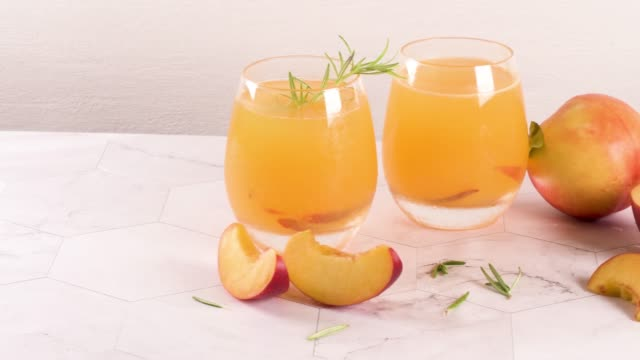 Summer cold drinks Homemade peach juice with ice cubes and rosemary leaves in glass on marble stone background. peach stock videos & royalty-free footage