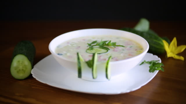 summer cucumber soup with vegetables on a wooden table video