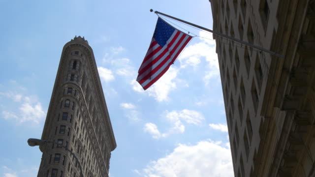 summer day light new york city flat iron bulding american flag waving 4k usa video