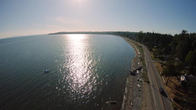 小さな町への海岸風光明媚なルート上の夏のドライブ空中 ビデオ