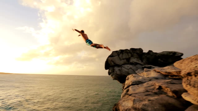 Summer Extreme Sports Cliff Jumping Outdoor Lifestyle. Cliff Jumping at Sunset. Young Man Jumps off Cliff Into Water. Summer Extreme Sports Outdoor Lifestyle. Cliff Jumping at Sunset. cliffs stock videos & royalty-free footage